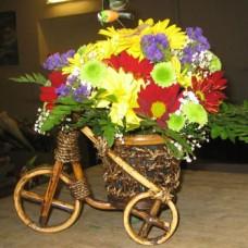 Корзина с цветами в форме велосипеда из хризантем, гербер и статицы